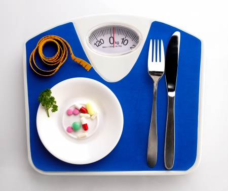 white plate with leaf of curly parsley and supplement, measuring tape, spoon and knife on blue scale, top view photo