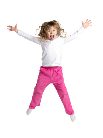niños danzando: retrato de una niña feliz en ropa casual blanco y rosa con rizos largos saltando aislado en blanco Foto de archivo