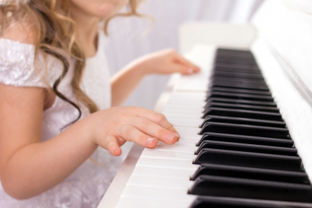 elation: little girl with  long curls in white feshion dress playing on white piano, close-up Stock Photo