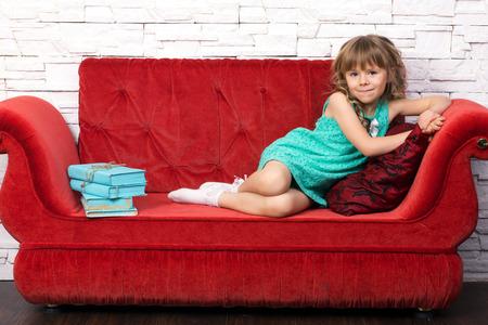 hermosa niña en traje de moda con largo rizos rubios aprender sobre la tos rojo, cerca de aprender pila de libros antiguos Foto de archivo