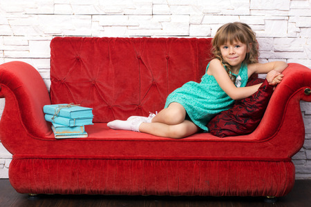 green couch:  little beautiful girl in fashion dress with long blond curl learn on red cough, near learn pile of old books