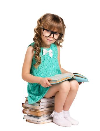 petite fille avec robe: belle petite fille aux longs cheveux bouclés, dans le grand verre optique assis sur la pile de vieux livres tenant un livre ouvert et regarder la caméra isolée sur fond blanc