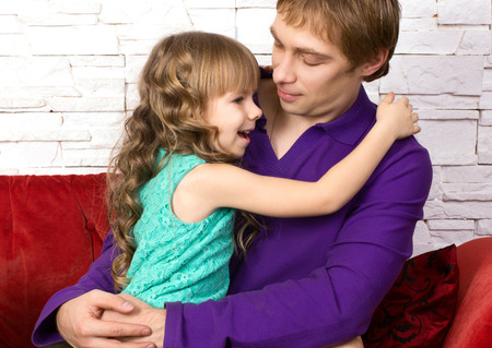 communicated: father and little daughter sitting on red sofa with toy  on modern background and  communicated
