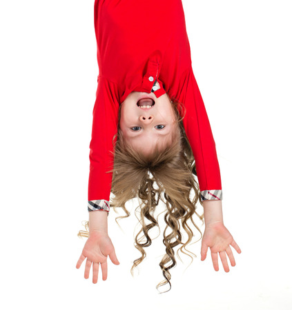 Little beautiful girl with long blond curls hanging upside down isolated on white photo
