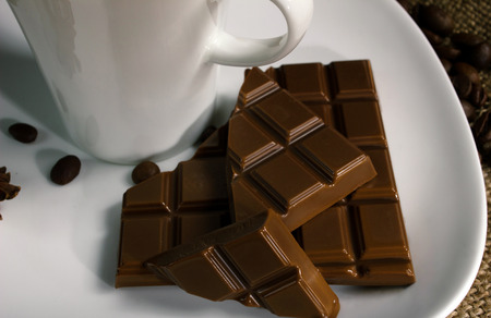 slice of beautiful chocolate and white cup on white plate, close up  photo