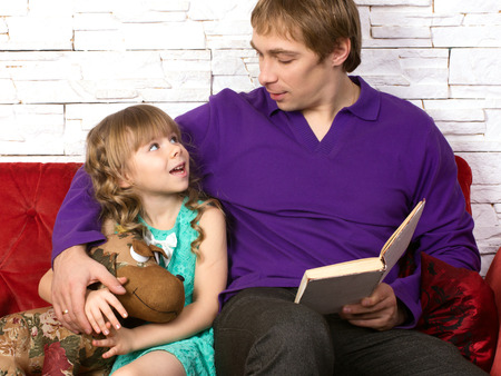 communicated: father and little daughter sitting on red sofa with toy and book looking at each other and  communicated