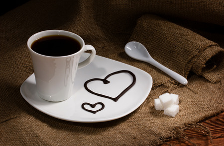 close-up of coffee in white cup on white plate, near - ceramic spoon and sugar lumps on burlap, on plate drawn hearts  photo