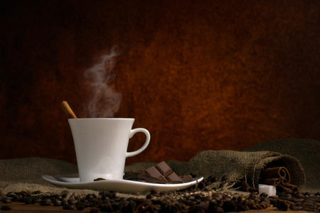 cinnamon stick: coffee with steam in white  cup on saucer, and cubes sugar on burlap wooden table on dark brown background