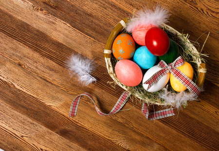 colorful eggs in straw basket and feathers of bird on wooden background photo