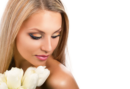 portrait of a young blond barred woman with bunch of white tulip looking down on white background photo