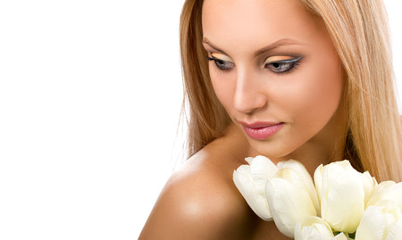 young blond barred woman with bunch of white tulip looking down on white background photo