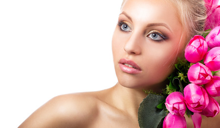 portrait of a young blond barred woman with grey eyes and bunch of pink tulips on white background photo