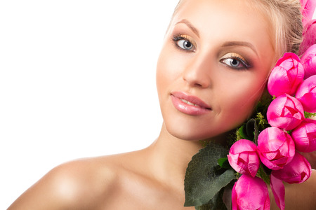 portrait of a young blond naked woman with grey eyes and bunch of pink tulips on white background photo