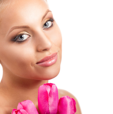 portrait of a young smiling  blond woman with grey eyes and bunch of pink tulip looking at camera on white background photo