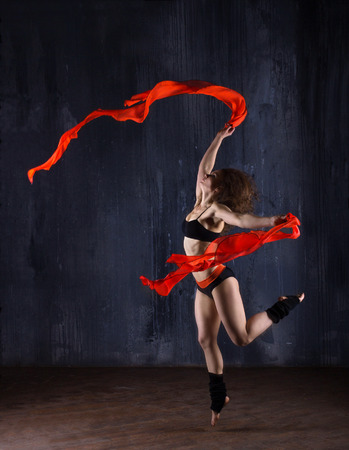 young woman with red ribbons dancing and jumping  on dark modern background photo