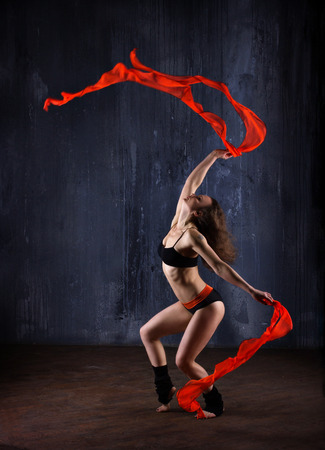young woman with red ribbons dancing indoor on dark modern background photo