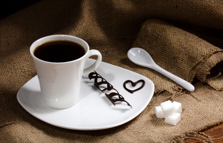on white plate - coffee in white cup and chocolate slice and chocolate heart, near - ceramic spoon and sugar lumps on sacking, on wooden table  photo
