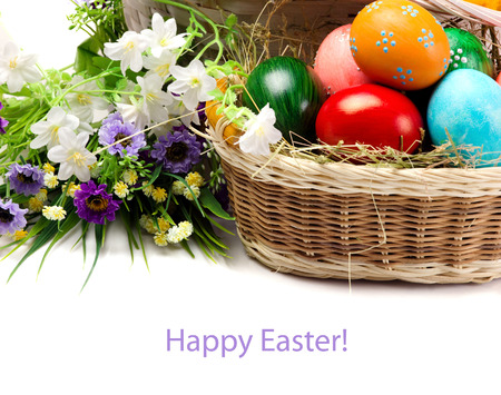 easter colorful eggs in basket and bunch of flowers on white background
