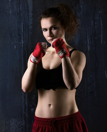 stance: portrat of a sexy young woman boxer in red and black clothes  ready to fight  on dark grey background  Stock Photo