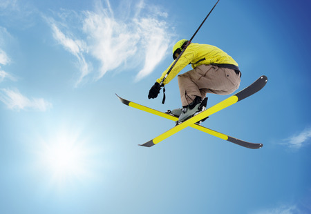 extreme weather: jumping skier  on blue sky background Stock Photo