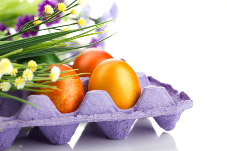 close-up easter colorful eggs in violet tray and  bunch of flowers  on white background photo