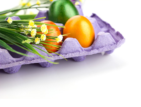 easter colorful eggs in tray and  bunch of flowers and  blurred eggs with flowers on light background photo