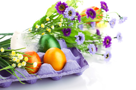 easter colorful eggs in violet tray,  bunch of flowers and feather on light and white background photo