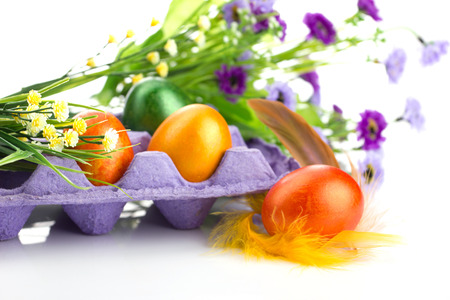easter colorful eggs in tray, feather,  bunch of flowers and  blurred eggs with flowers on white background photo