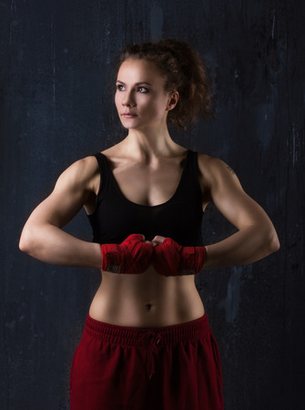 Portrait of a sporty young brunette woman with beautiful musculature on dark grunge background photo