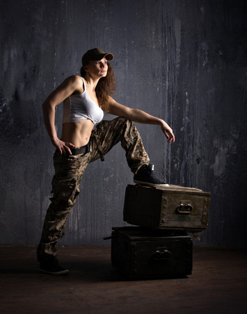 army girl: adult girl in camouflage clothes standing on military boxes on dark grunge wall background Stock Photo