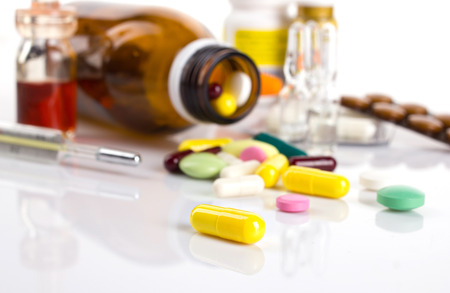 drug in yellow capsule on white table and blurred background with different medicaments in blisters and bottle and thermometer