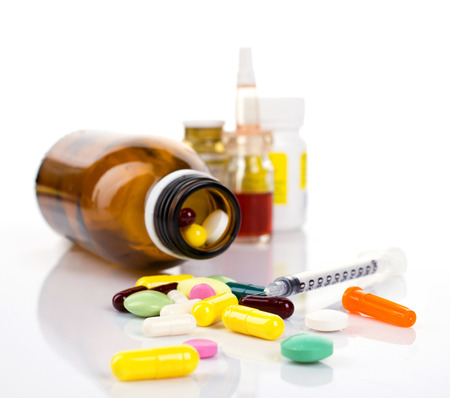 insulin bottle: insulin syringe and colorful pill and capsules from glass bottle on blurred containers and white background