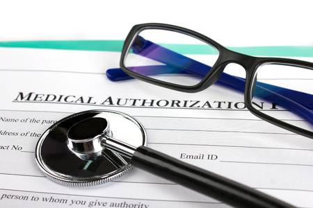 close-up optical glasses,  stethoscope and m edical authorization form on green board on white background