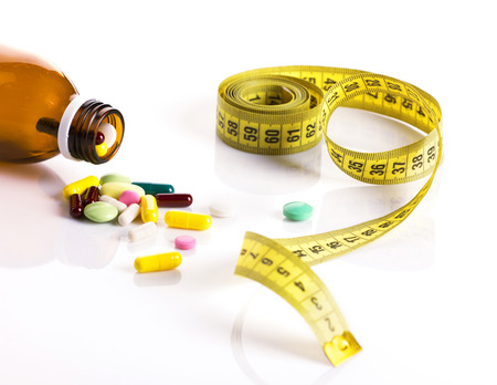 diet concept - colorful pills from bottle and yellow centimeter on the white background