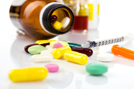 insulin bottle: insulin syringe and colorful pill and capsules from glass bottle on white background