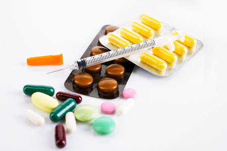 colorful drugs in tablets  and capsules and insulin syringe on white background