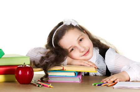 weariness  schoolgirl with long curl in black and white uniform sitting at the table with  many colorful books, pencils, red beautiful apple  and laying head on her hand, on white background photo