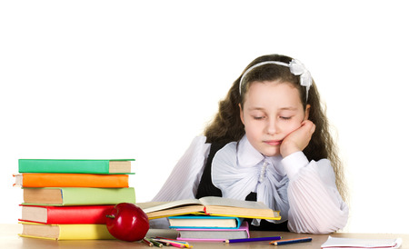 jaded: tiredness little girl in black and white uniform sitting  at the table and looking in book, near - many books and red apple, on white background