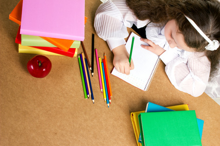 child studying: beauty preschooler girl  in white and black uniform diligently writing in copybook, near -  red apple, many colorful books and pencils, top view Stock Photo