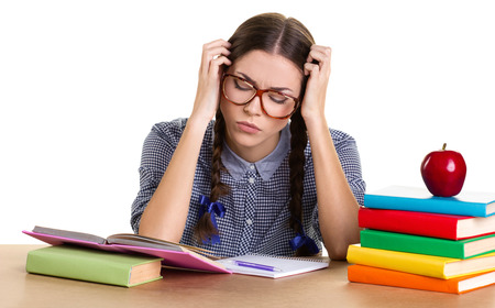 jaded: teen girl sitting  at the table, hold her head and looking in book, near - many books, copybook, pen and red apple on white background