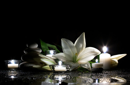 spa still life with freshness white lily, stack of several stones and  burning candles on  black bright table with water drop, and black background