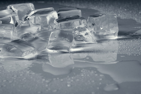 pile of different ice cubes on reflection table with water drop, light grey color   photo