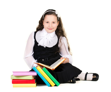 schoolgirl uniform: schoolgirl in black and white uniform sitting with many colorful books isolated on white