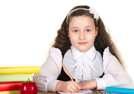 beautiful girl in white and black uniform sitting at the table and drawing in copybook, near learn red apple, pensils and stack of colorful books on white background  photo
