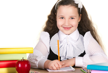 smiling toothlessing girl drawing in copybook, near learn red apple and  stack of colorful books on white background photo