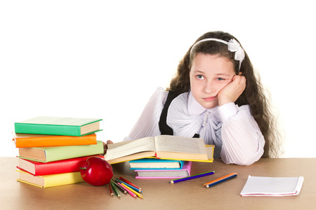 jaded: tired little girl in black and white school form sitting  at the table, looking in book, near - many books and red apple, isolated on white Stock Photo