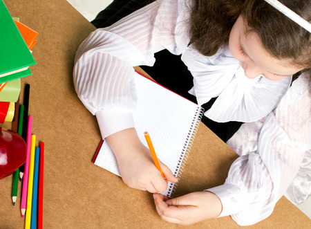 beauty little girl  in school form writing in copybook, near -  red apple, many colorful books and pencils, top view photo