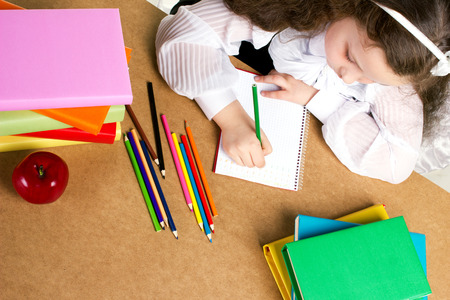 beauty little girl  in school form diligently writing in copybook, near -  red apple, many colorful books and pencils, top view photo
