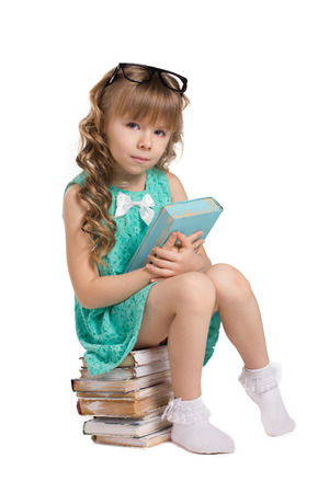 little beautiful girl with long curls, in big optical glass sit on pile of old books holding  book and  look at camera isolated on white Reklamní fotografie