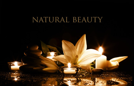 beauty composition with white lily, burning candles and stack of stones in gold and black colors